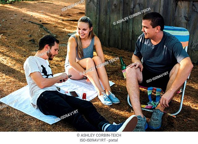 Three adult friends relaxing outside hut in forest