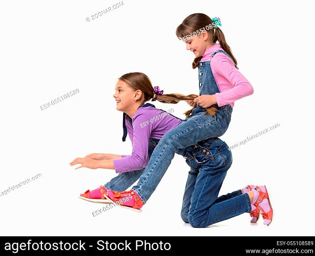 Girl rides another girl on herself on a white background