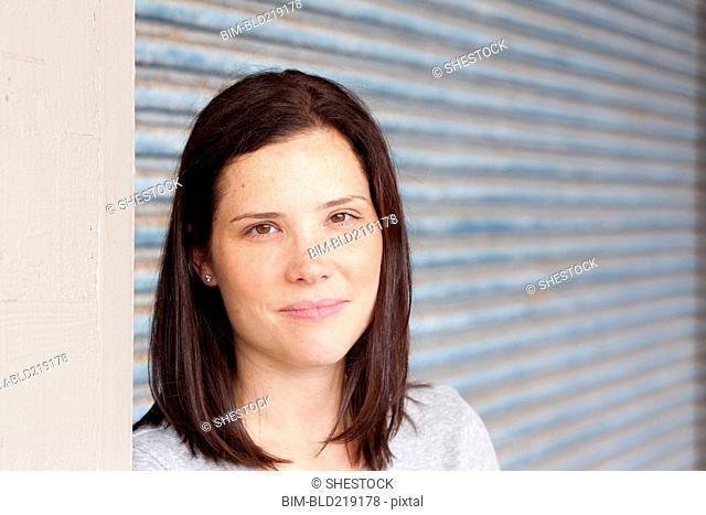 Close up of smiling woman standing by garage door