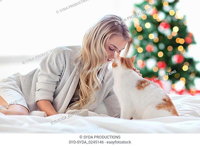 happy young woman with cat in bed at christmas