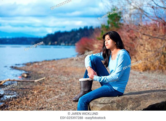Young biracial teen girl in blue shirt and jeans sitting along rocky lake shore on bright overcast day outdoors