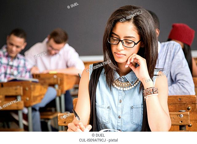 Female student, sitting at desk in classroom, writing