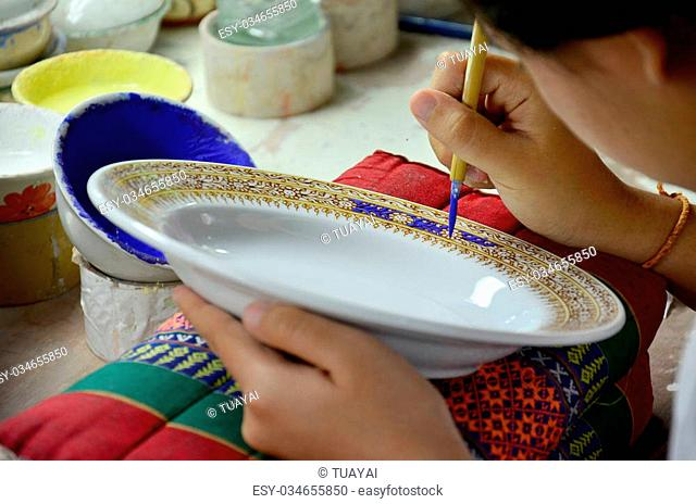 Thai people woking process paint Ceramic Benjarong is traditional thai five basic colors style pottery at workshop on August 8, 2015 in Samutsakhon, Thailand