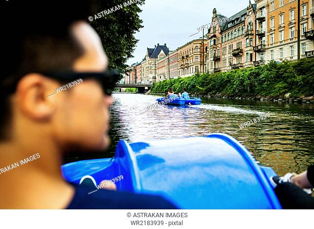 Rear view of man pedaling boat on river in city