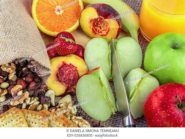 Fruits and nuts background with a mix of apples, oranges, bananas, peach, strawberries and different types of nuts, like walnuts, almonds, hazelnuts