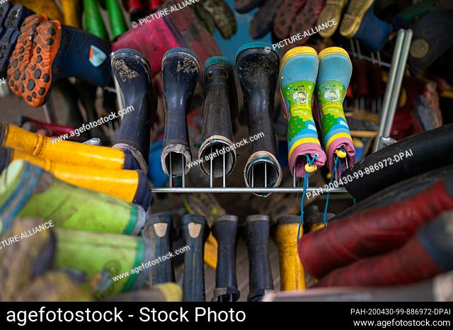28 April 2020, Lower Saxony, Lüneburg: Rubber boots hang on the active playground. In view of the closed playgrounds in Lower Saxony