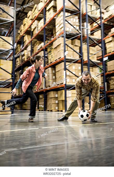 Two warehouse workers playing soccer during a work break in a distribution warehouse