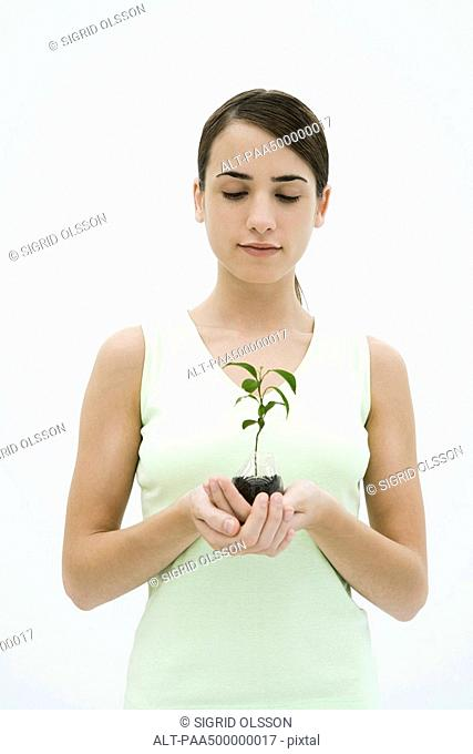 Woman holding potted seedling, looking down