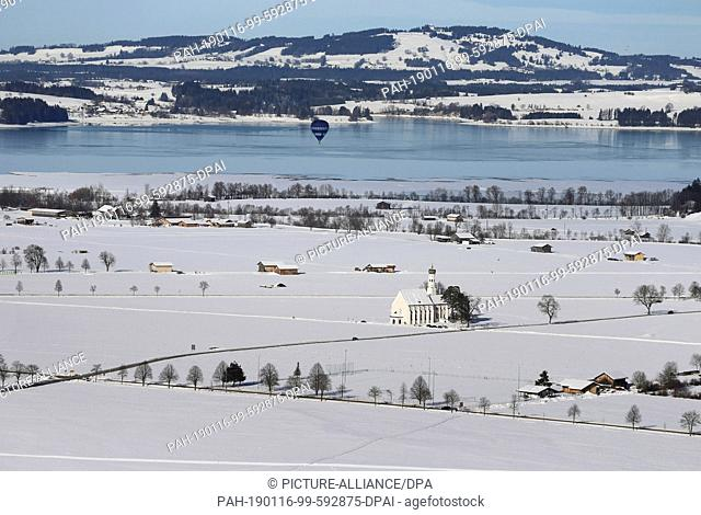 16 January 2019, Bavaria, Schwangau: A hot-air balloon rides over Lake Forggen and the Sanctuary of St Coloman, set in a snow-covered landscape