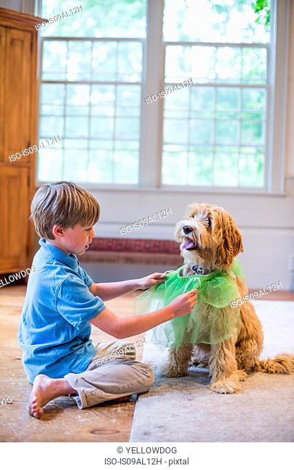 Young boy playing dress up with pet dog