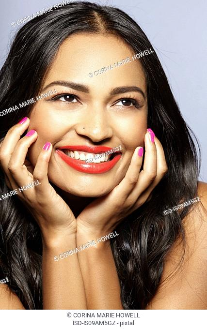 Female model smiling, face resting on hands