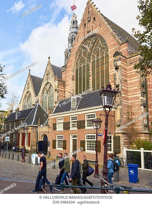Tourists pulling suitcases passing Oude Kerk (old church), Oudekerksplein, Amsterdam, Netherlands. Amsterdam's oldest building founded in 1213 and consecrated...