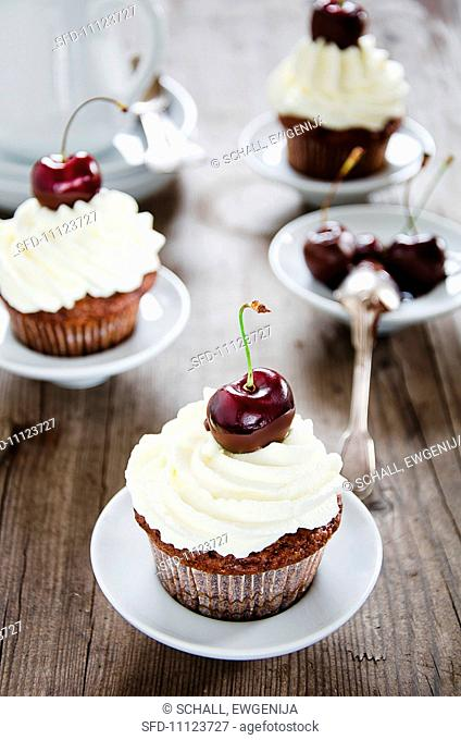 Chocolate muffins with cream and cherries