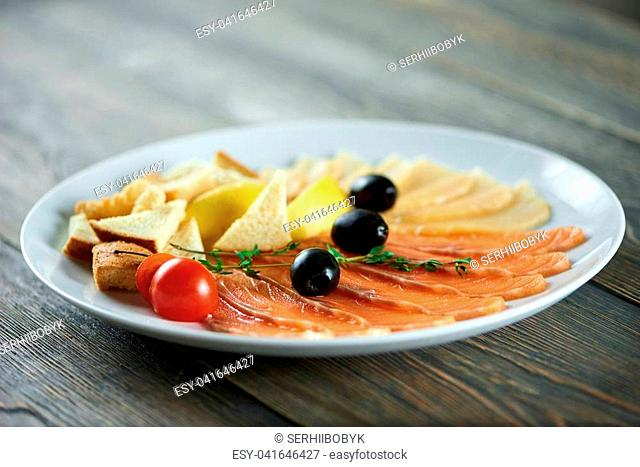 Close-up of white plate with the delicios appetizers set: fresh tomatoes, black olives, white bread pieces, smoked salmon slices and cheese
