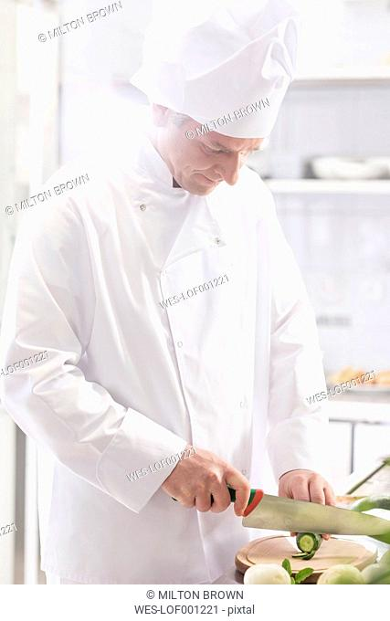 Chef in kitchen cutting cucumber