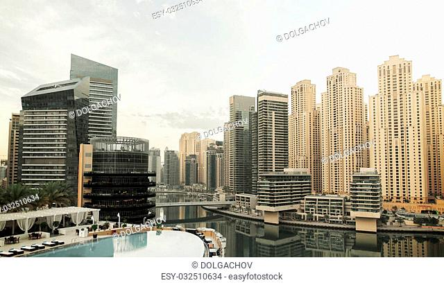 cityscape, travel, tourism and urban concept - Dubai city district skyscrapers and seafront with hotel infinity edge pool