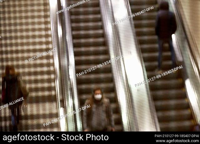 27 January 2021, North Rhine-Westphalia, Cologne: People ride behind a grid on an escalator. Chancellor Merkel and the heads of state governments have agreed to...