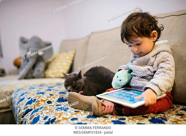 Baby girl sitting on couch watching videos on a tablet with a cat