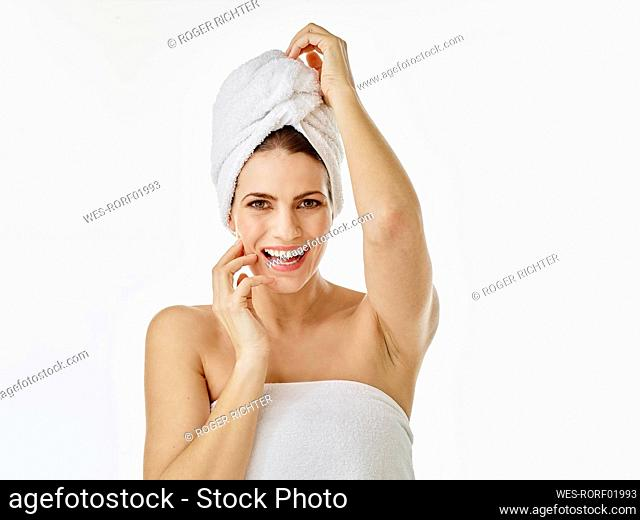 Portrait of happy woman with hairs wrapped in towel against white background