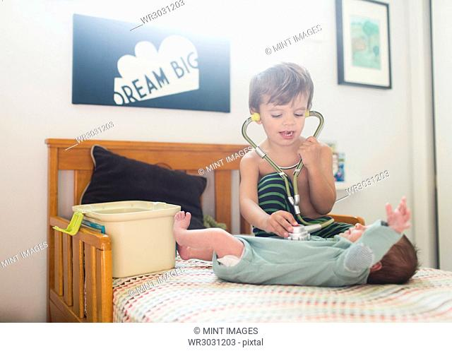 Young boy sitting on a bed, listening to small baby's heartbeat using a stethoscope
