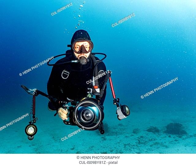 Underwater view of male diver with under water camera, portrait, Raja Ampat, Sorong, Nusa Tenggara Barat, Indonesia