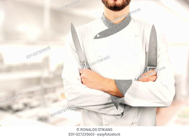 chef standing in the restaurant kitchen with knives in hands