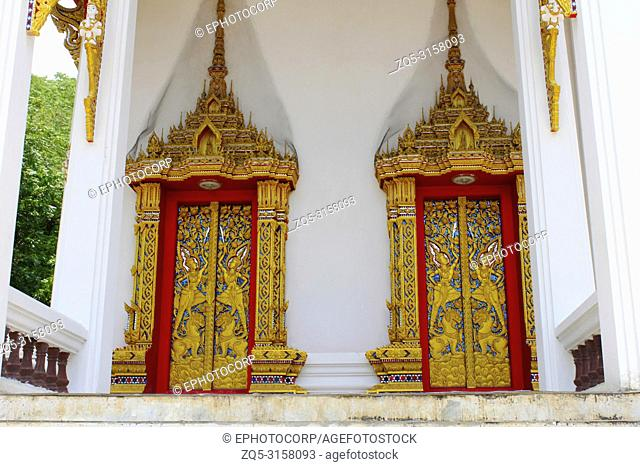 Doors and windows of the temple adorned by intricate wooden carvings in golden color depicting Buddha's life familiarized by Jataka Tales