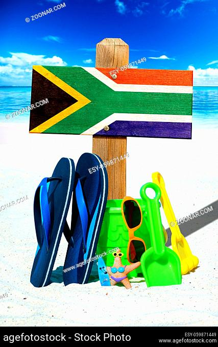 Holzschild mit Südafrika Flagge am Strand