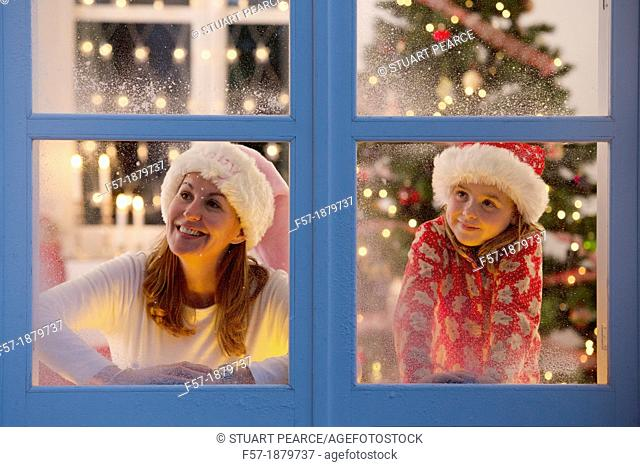Mother & daughter looking out of the window waiting for Santa to arrive