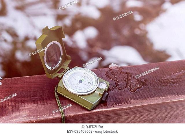 Compass instrument on wooden railing. Mountain hiking trails. Winter mountain trip concept