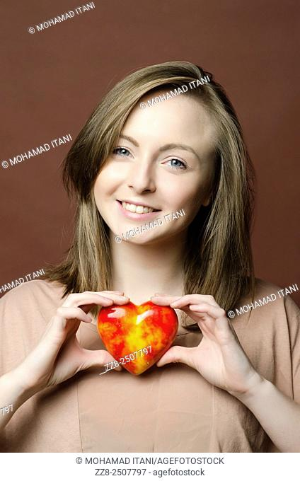 Happy young woman holding a marble heart smiling