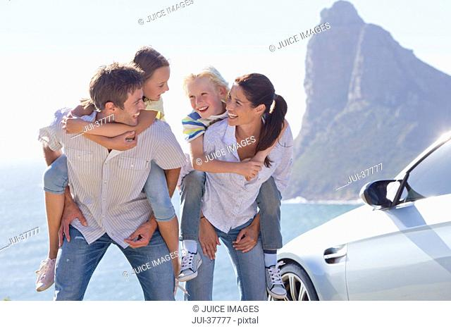 Happy family piggybacking outside car near ocean