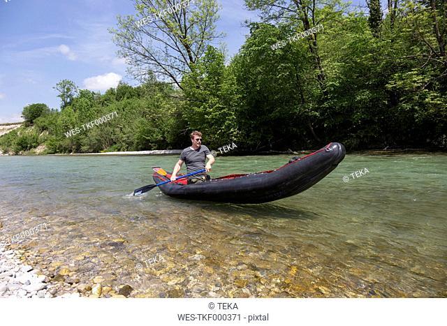 Germany, Bavaria, man paddling in rafting boat on Isar River