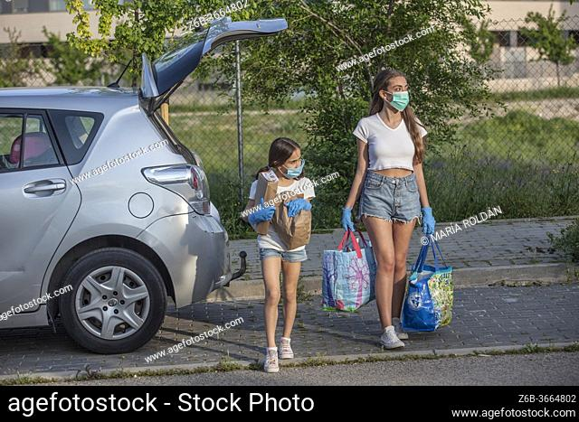 Girls wearing masks and gloves going to cross the street with shopping bags