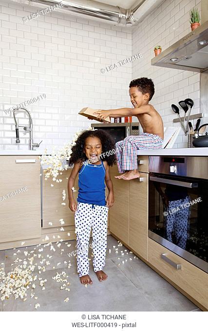 Little boy spilling popcorn on his sister's head