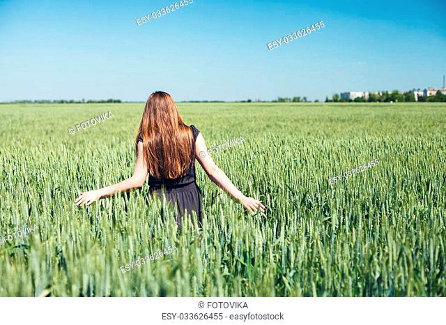 The beautiful girl is on a wheaten field