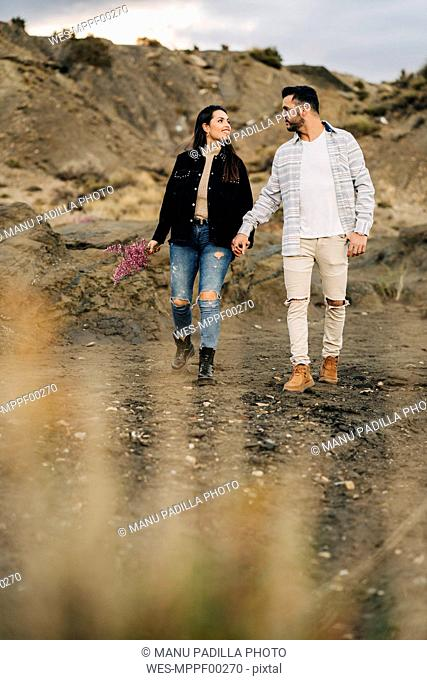Young couple walking hand in hand through desert landscape, Almeria, Andalusia, Spain
