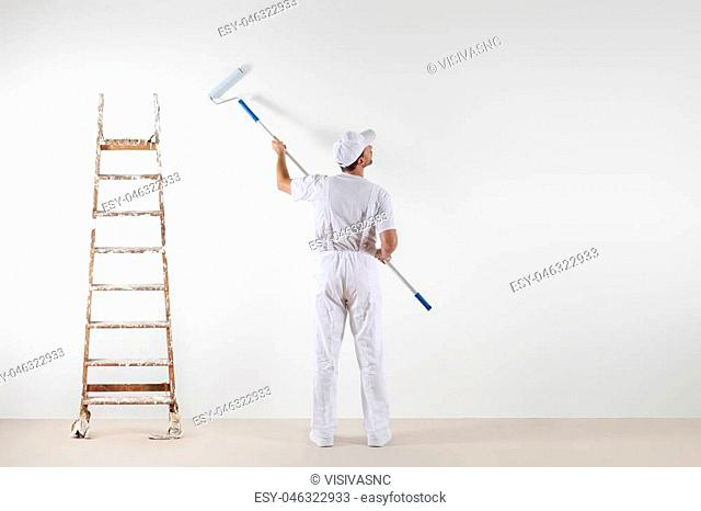 Rear view of painter man looking at blank wall, with paint stick roller and wooden ladder, isolated on white room