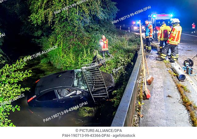 13 July 2019, Baden-Wuerttemberg, Stutensee: A car fell over a bridge railing into a creek. The cause of the accident is still unclear, according to the police