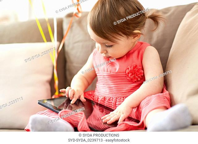baby girl with tablet pc sitting on sofa at home