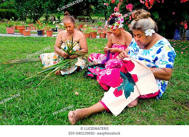 Portrait of Polynesian Pacific Island Tahitian mature females sewing Tivaivai and weaving a hat knees out of palm leaves outside their home in Aitutaki lagoon...