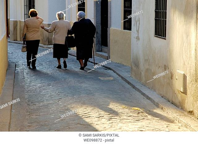 Three women walking down a cobbled alley, Cordoba, Andalusia, Spain