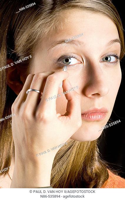 Young girl applying eyeliner