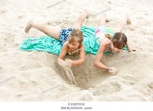 Caucasian girls playing in the sand on the beach