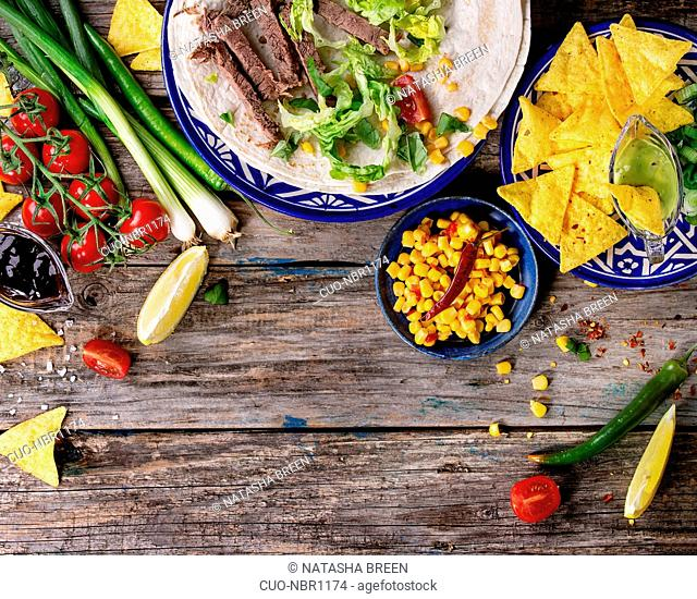 Food background with nachos chips and ingredients for making tartilla and burrito. Onion, tomatoes, chili peppers, beef, tortillas and corn with deeps over old...