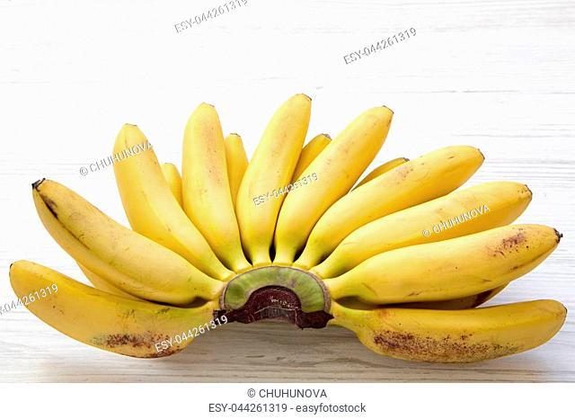 Bunch of baby banana on a white wooden background. Closeup