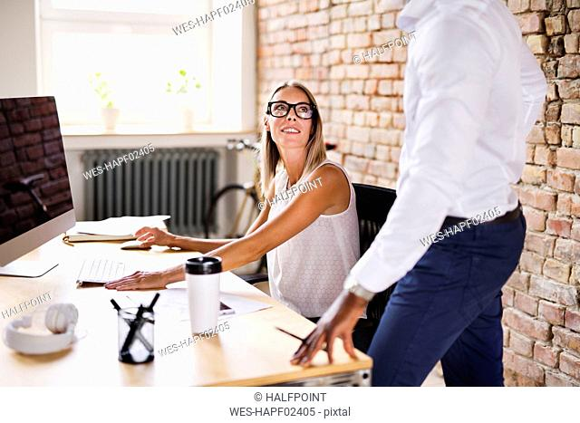 Two colleagues working together at desk in office