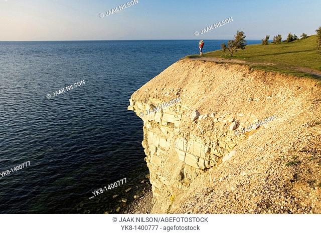 Woman Holding Baby and Standing on Steep Panga Cliff by Sea in Saare County, Estonia