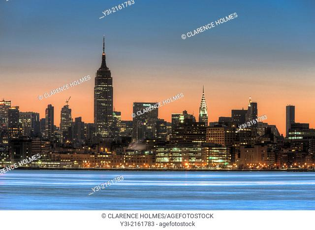 The sky begins to lighten with hints of pre-sunrise orange color over the Empire State Building and other buildings of the Manhattan skyline in New York City