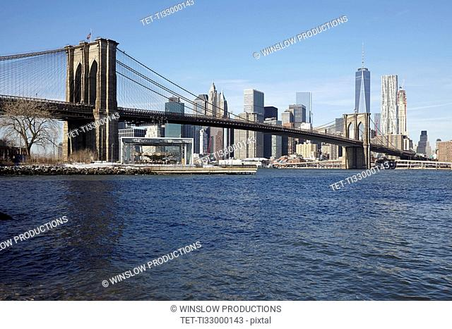 View of waterfront cityscape with suspension bridge